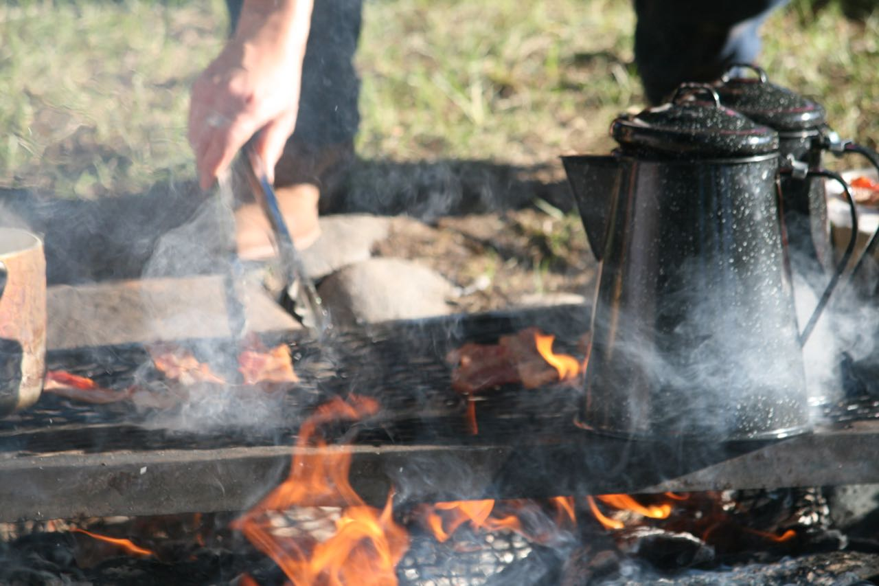 A hand with tongs cooking bacon and coffee over a campfire - Lazy L&B Dude Ranch Wyoming