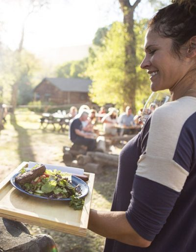 Lady Holding a Plate of Salad and Steak at campfire cookout - Campfire Cowboy Breakfast - Lazy L&B Dude Ranch Wyoming
