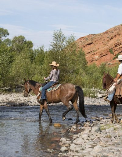 3 Riders on Horseback Crossing the East Fork of the Wind River with red cliffs in the background - Lazy L&B Guest Ranch Wyoming