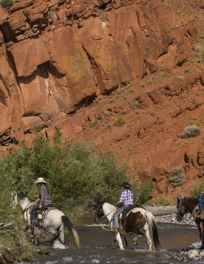 Wrangler and 2 children crossing the East Fork River with a red rock cliff in background - Lazy L&B Dude Ranch Wyoming