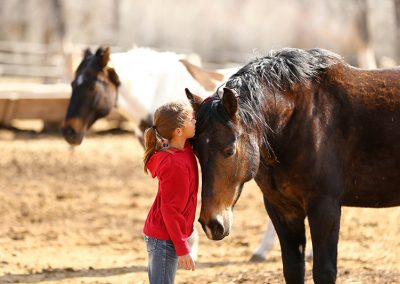 Young Girl whispering into the ear of a brown horse whose head is bent down toward her with a paint horse in background - Lazy L&B Dude Ranch Wyoming