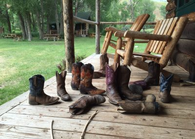 Lots of pairs of kids cowboy boots strewn on front porch of log cabin - Lazy L&B Dude Ranch Wyoming