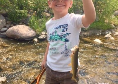 Young smiling Boy standing in a river holding up a cutthrroat trout in one hand and a fishing net in the other - Lazy L&B Dude Ranch Wyoming