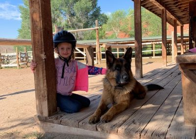 Young Girl with German Shepherd Dog on porch of log cabin - Lazy L&B Dude Ranch Wyoming