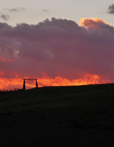 Beautiful fiery red and orange sunset with an overhead gate on a ridge - Lazy L&B Guest Ranch Wyoming