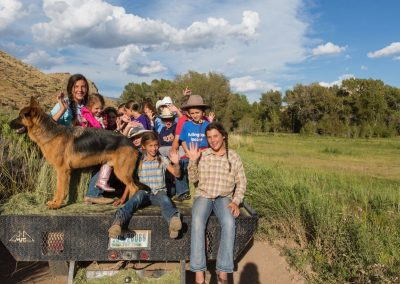 Smiling Children and German Shepherd Dog Sitting on hay bales on the back of a flatbed pickup truck going to a campfire cookout - Lazy L&B Dude Ranch Wyoming